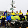Members of the AUV team at Davis research station standing beside the AUV on a trailer.