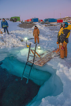Australian expeditioners stand around a hole cut in the sea ice at Mawson research station as they prepare the 'swimming pool' for a midwinter dip