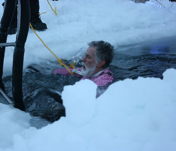 Expeditioner wearing colourful shirt taking a dip in the Casey sea ice swimming pool.