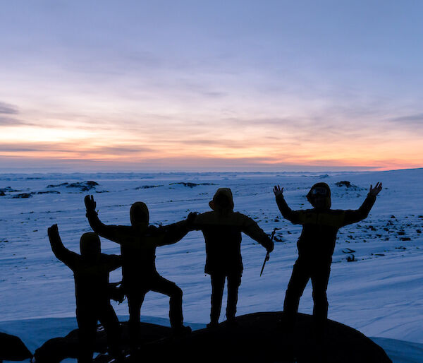 Photo of a group silhouetted up on a rocky outcrop
