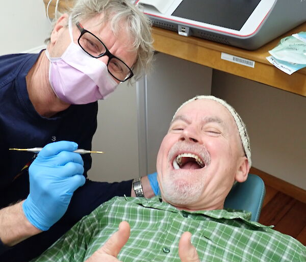 Doctor gives the thumbs up while lying down in the dental suite