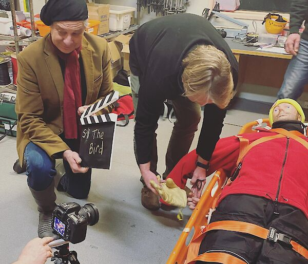 Two expeditioners prepare a scene with a CPR dummy for filming a video