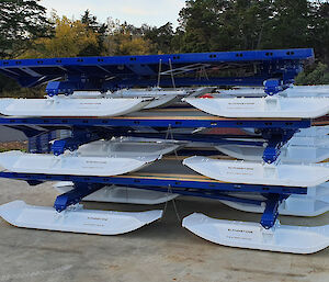 Three steel sleds with skis, stacked on top of each other.
