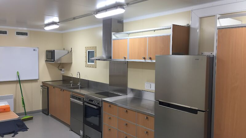 View of the kitchen in the traverse dining/living van showing the fridge, oven, dishwasher and stainless steel benchtops.