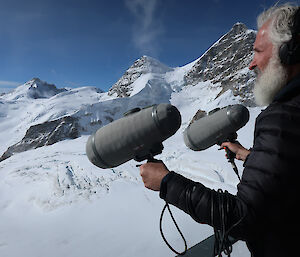 A man holding two long microphones pointed towards a snowy mountain range