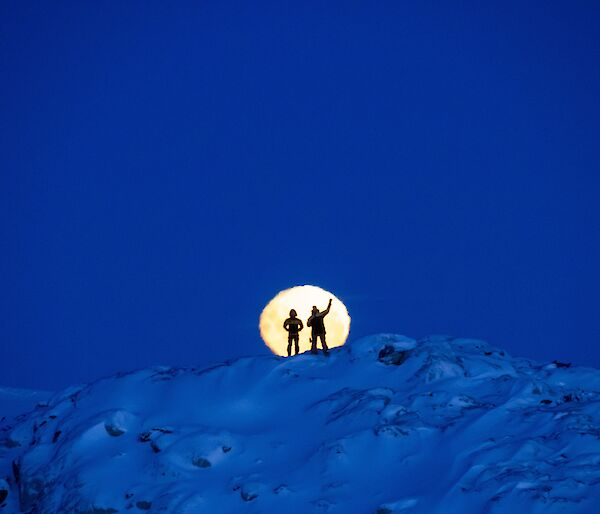 Two expeditioners silhouetted against the moon whilst standing on a snowy mountain
