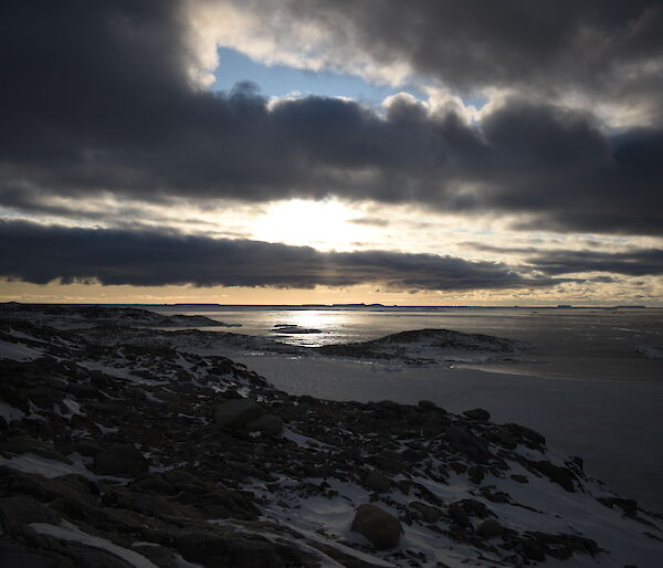 A constrasting sky with blue showing through and dark but light rimmed clouds looking towards the mouth of Newcomb Bay
