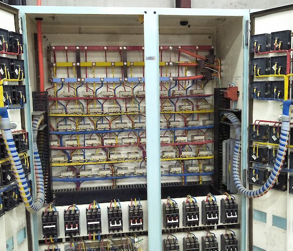 A large electrical switchboard with lots of wires