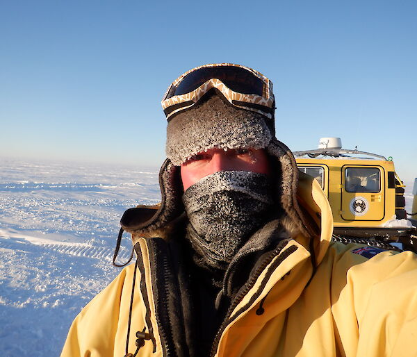 Portrait of expeditioner with cold weather gear.  Only eyes are uncovered on his face.  Ice in background.