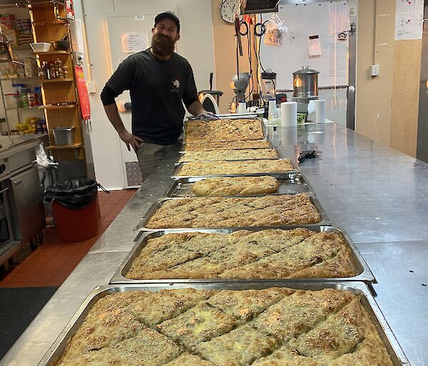 7 trays of fresh made borek on a kitchen bench with an expeditioner smiling to camera