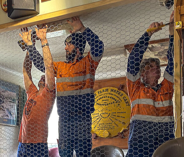 Three tradesmen putting up a chicken wire wall in the Mess