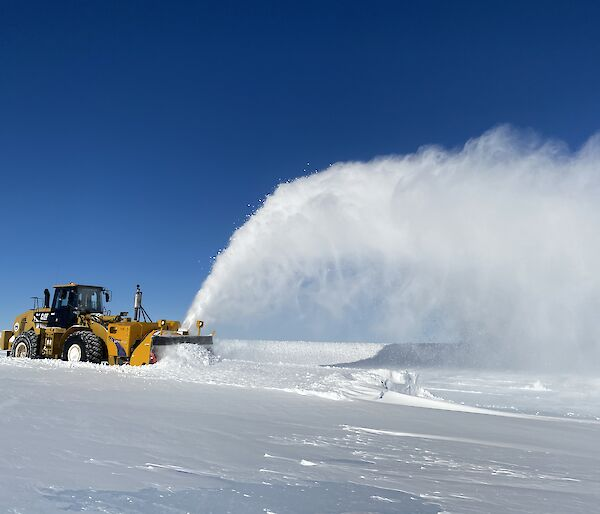 An Øveraasen snow blower on the runway with a plume of snow flying in the air