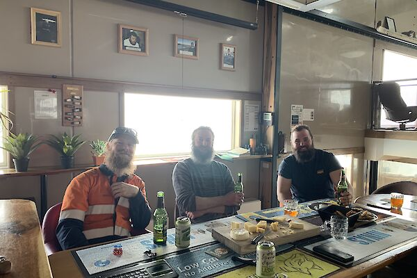 Three plumbers sitting at a table drinking beer