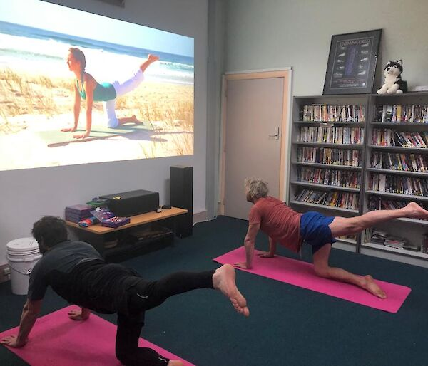 Two expedioners on yoga mats watching a yoga tutorial on screen and replicating the pose