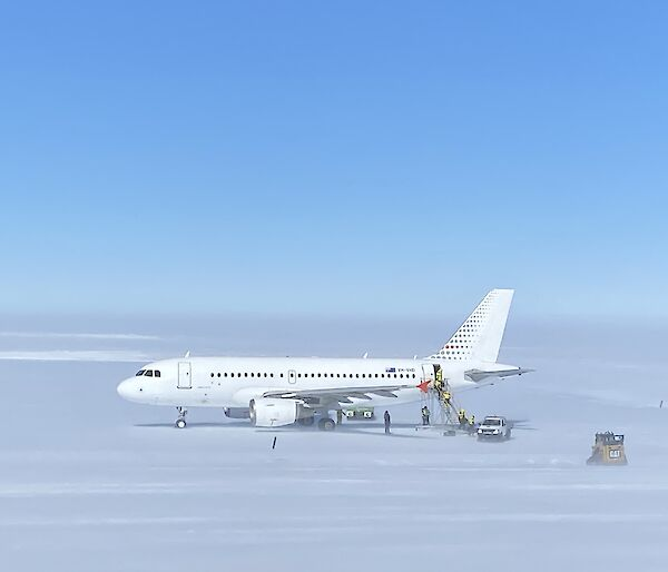 A319 Airbus sitting on the ice runway with support crew surrounding