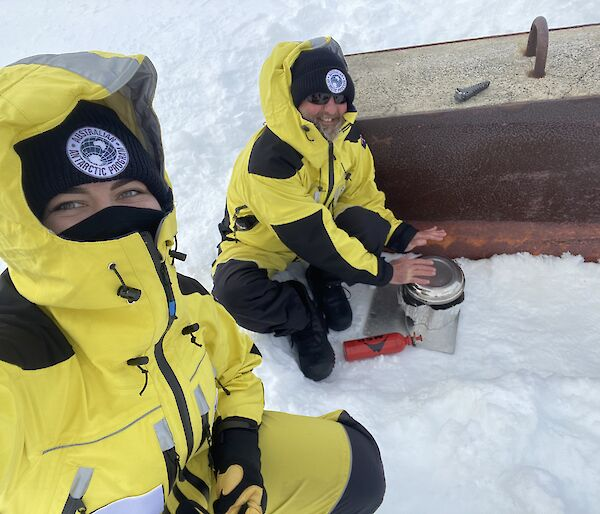 Two expeditioners preparing a meal in the snow.