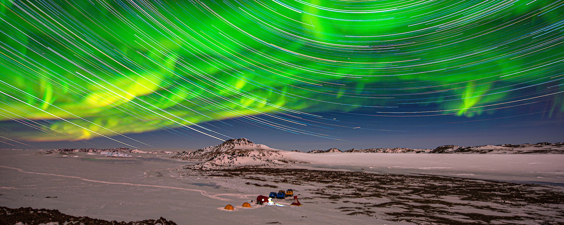star trails and aurora over icy plain in twilight