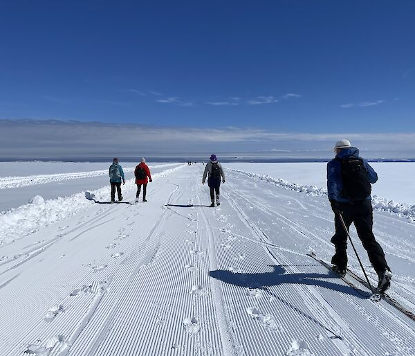 3 people walking. 1 person cross-country skiing. Groomed snow track. Blue skies. Ocean in the background.