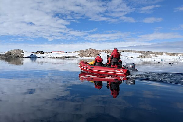 Inflatable boat with expeditioners. Still water conditions. Station in the background.