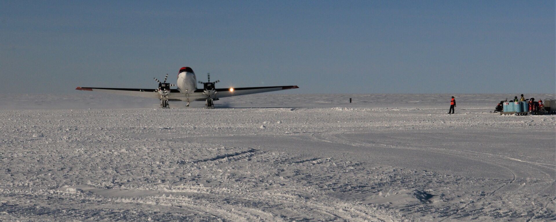 a plane lands on snow runway