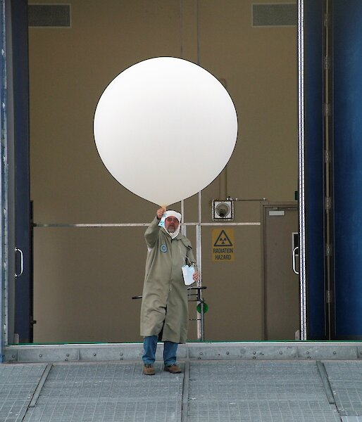 man in protective gear with large white balloon and ozone sonde