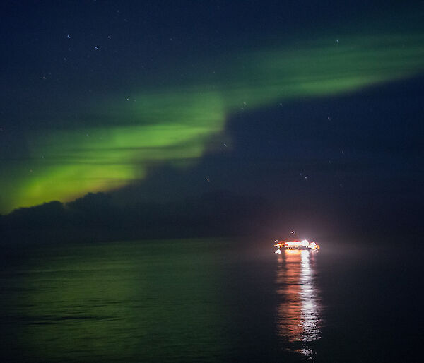 A bright green Aurora lights the dark sky.  The lights of a boat on the water are reflected in the water.