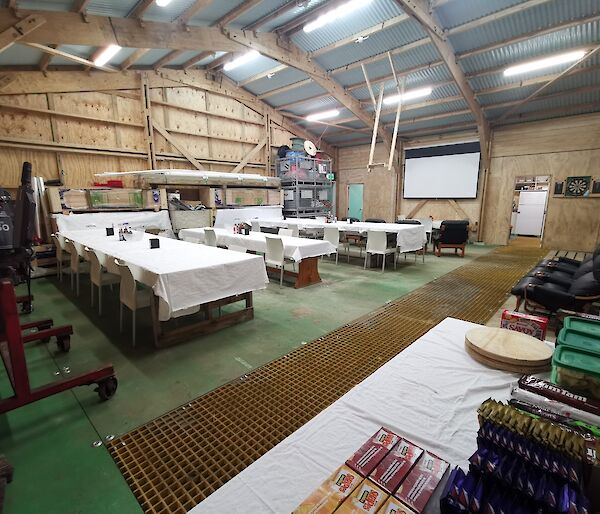 A large shed with wooden walls and a corrugated room, set up with dining tables covered in white table cloths, loungers facing a large white screen on the wall and a snack table in the  foreground