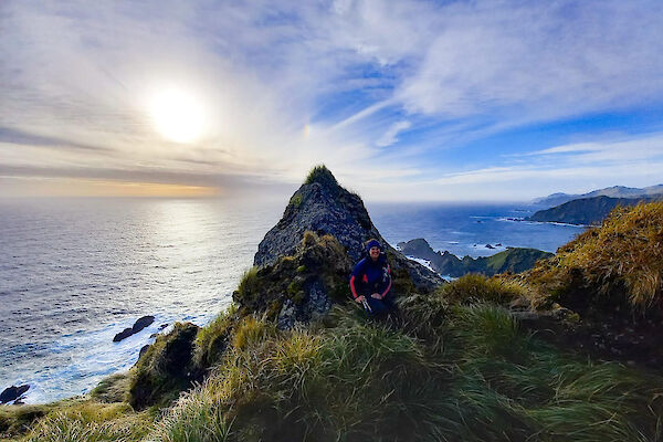 An expeditioner resting in the grassy tussocks against a large pointed rock with the sea and blue sky behind it