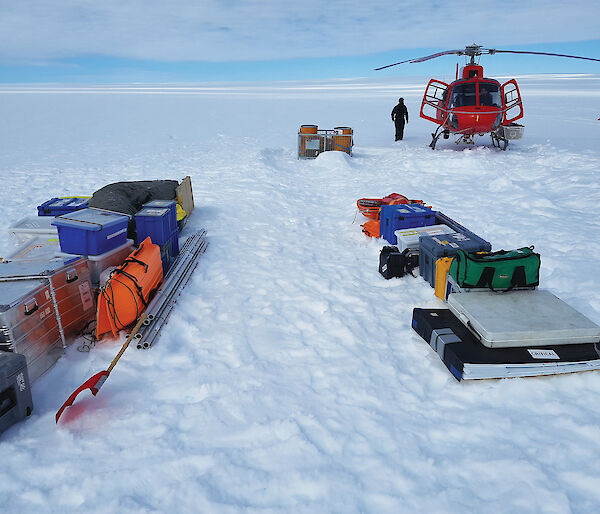 Equipment and a helicopter on a snow-covered glacier in Antarctica.