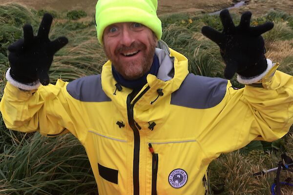 A man in bright yellow cold weather clothing, gloves and a bright hat holds his hands up to camera and smiles