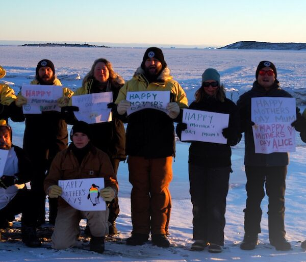 A group of expeditioners standing in the snow holding up Happy Mother's Day signs